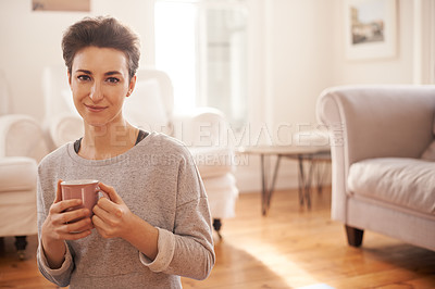 Buy stock photo Cropped shot of an attractive young woman having a cup of coffee in the living room at home