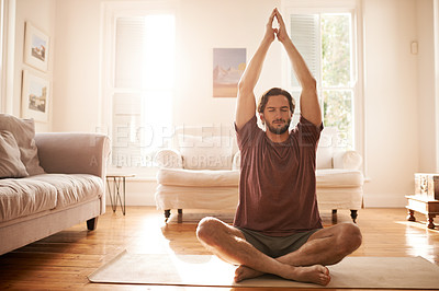 Buy stock photo Shot of a handsome young man practicing yoga in the living room at home