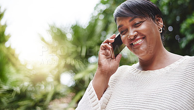 Buy stock photo Shot of a mature woman talking on a cellphone outdoors