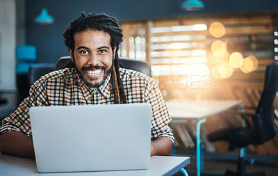 Buy stock photo Cropped portrait of a handsome young male designer working on his laptop in the office