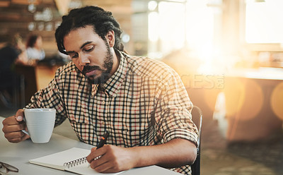 Buy stock photo Cropped shot of a handsome young male designer writing in his notebook