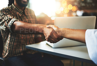 Buy stock photo Cropped shot of two unrecognizable designers shaking hands while sitting in the office