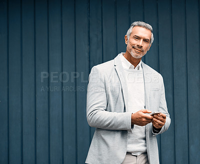 Buy stock photo Cropped shot of a smartly dressed mature businessman using a cellphone outside