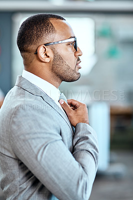 Buy stock photo Shot of a young businessman adjusting his tie in an office