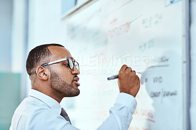 Buy stock photo Shot of a young businessman writing notes on a whiteboard in an office