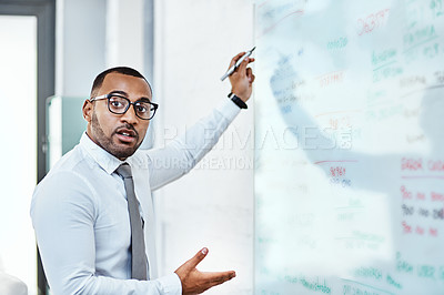 Buy stock photo Portrait of a young businessman brainstorming on a whiteboard in an office
