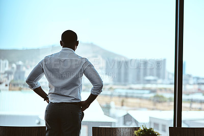 Buy stock photo Rearview shot of a businessman looking out the window in an office