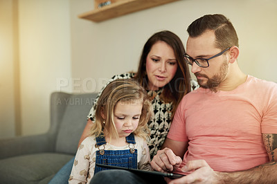 Buy stock photo Shot of young man and woman using a digital digital with their daughter at home