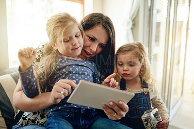 Buy stock photo Shot of young woman using a digital digital with her daughter's at home