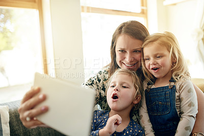 Buy stock photo Shot of a young woman taking selfies with her daughter's on a digital tablet at home