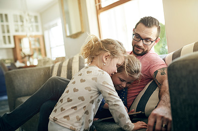Buy stock photo Shot of young man using a digital digital with his daughter's at home