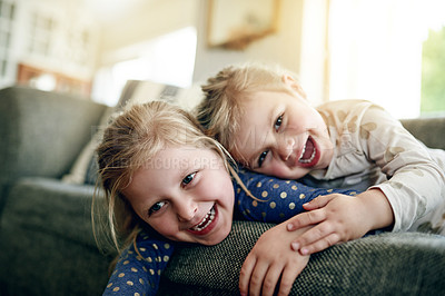 Buy stock photo Shot of two adorable little girls relaxing on the sofa at home