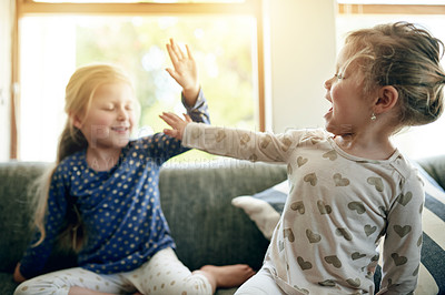 Buy stock photo Shot of two adorable little girls high fiving each other at home