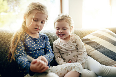 Buy stock photo Shot of two adorable little girls using a digital tablet together at home