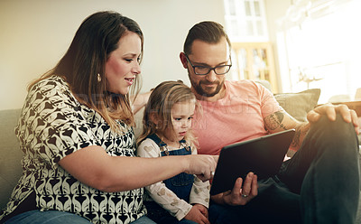 Buy stock photo Shot of a family using a digital tablet together at home