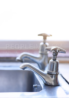 Buy stock photo Shot of two dripping taps waisting a little bit of water in a basin inside of a house during the day