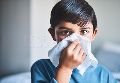 Buy stock photo Cropped portrait of an adorable little boy blowing his nose while standing in his home