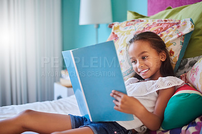 Buy stock photo Shot of an adorable little girl reading a book at home