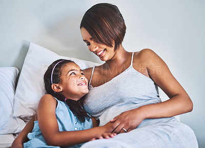 Buy stock photo Shot of a cheerful little girl relaxing on the bed with her pregnant mother at home during the day