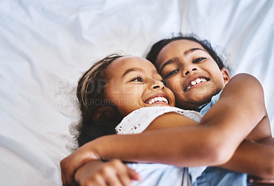 Buy stock photo Portrait of two cheerful little girls  with arms around each other while lying on a bed at home during the day