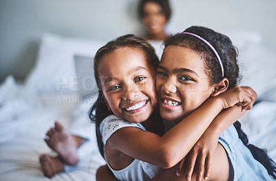 Buy stock photo Portrait of two cheerful little girls with arms around each other while their pregnant mother relaxes in the background with a laptop