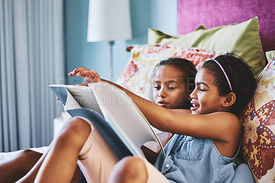 Buy stock photo Shot of two cheerful little girls reading a storybook together at home during the day
