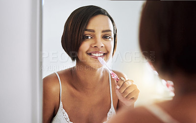 Buy stock photo Portrait of an attractive young woman brushing her teeth in the bathroom