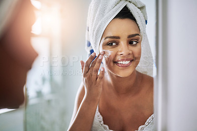 Buy stock photo Shot of an attractive young woman applying moisturizer to her face in the bathroom