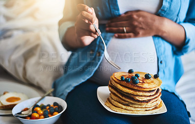 Buy stock photo Cropped shot of a pregnant woman eating delicious pancakes at home
