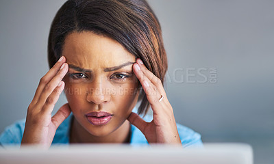 Buy stock photo Shot of an attractive young woman experiencing stress while using a laptop at home