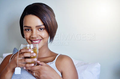 Buy stock photo Shot of an attractive young woman relaxing at home with a glass of tea