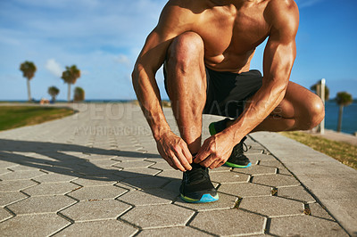 Buy stock photo Closeup shot of an unrecognizable man tying his shoelaces while exercising outdoors