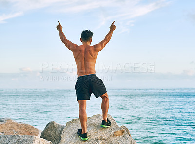 Buy stock photo Rearview shot of a handsome young man celebrating while exercising outdoors