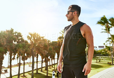 Buy stock photo Shot of a sporty young man standing outdoors