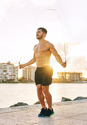 Buy stock photo Shot of a handsome young man using a skipping rope outdoors