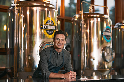 Buy stock photo Portrait of a cheerful young businessman seated at a table inside of a beer brewery  during the day