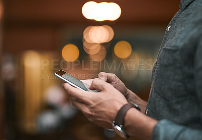 Buy stock photo Shot of an unrecognizable man browsing on a cellphone while standing inside of a beer brewery during the day