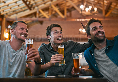 Buy stock photo Shot of three young cheerful men drinking beer at a table while taking a self portrait together inside of a beer brewery