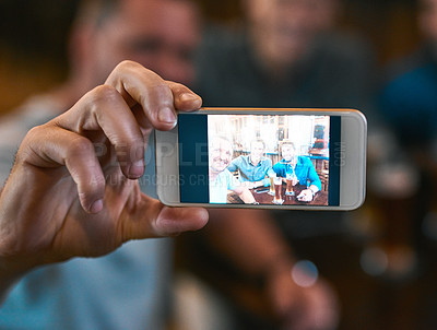Buy stock photo Shot of  three young men drinking beer at a table while taking a self portrait together inside of a beer brewery