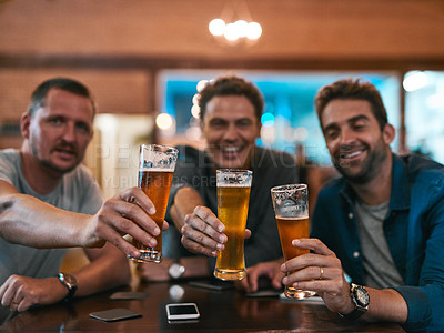 Buy stock photo Portrait of three cheerful young men having a celebratory toast with beer while sitting at a table inside of a beer brewery during the day