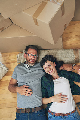 Buy stock photo High angle portrait of a happy couple relaxing together in their home on moving day