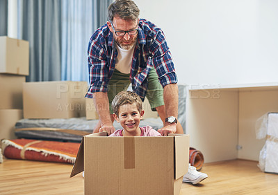 Buy stock photo Portrait of a happy father and son having fun together on moving day