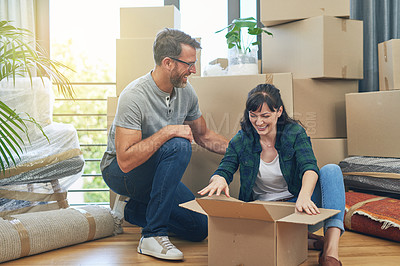 Buy stock photo Shot of a happy couple packing boxes in their home on moving day