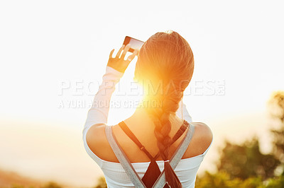 Buy stock photo Rearview shot of an unrecognizable woman taking a photo using her cellphone in nature