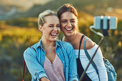 Buy stock photo Cropped shot of two beautiful female friends taking a selfie using a selfie stick in nature