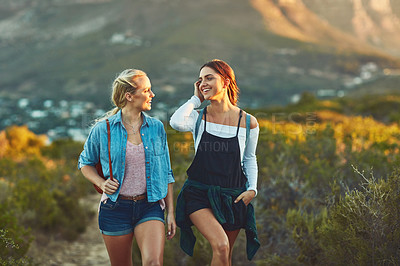 Buy stock photo Cropped shot of two beautiful female friends hiking in nature