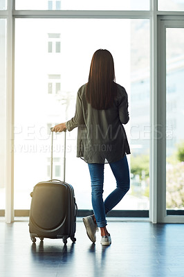 Buy stock photo Rearview shot of an unrecognizable woman looking out the window at an airport