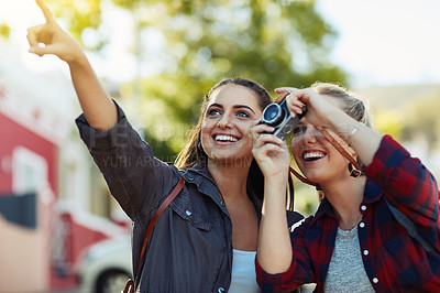 Buy stock photo Cropped shot two beautiful female friends taking photographs with a camera in the city