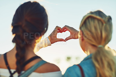 Buy stock photo Rearview shot of two unrecognizable female friends making a heart shape with their hands in nature