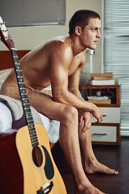 Buy stock photo Shot of a cheerful young man seated on his bed with a guitar next to him while being naked at home in the morning